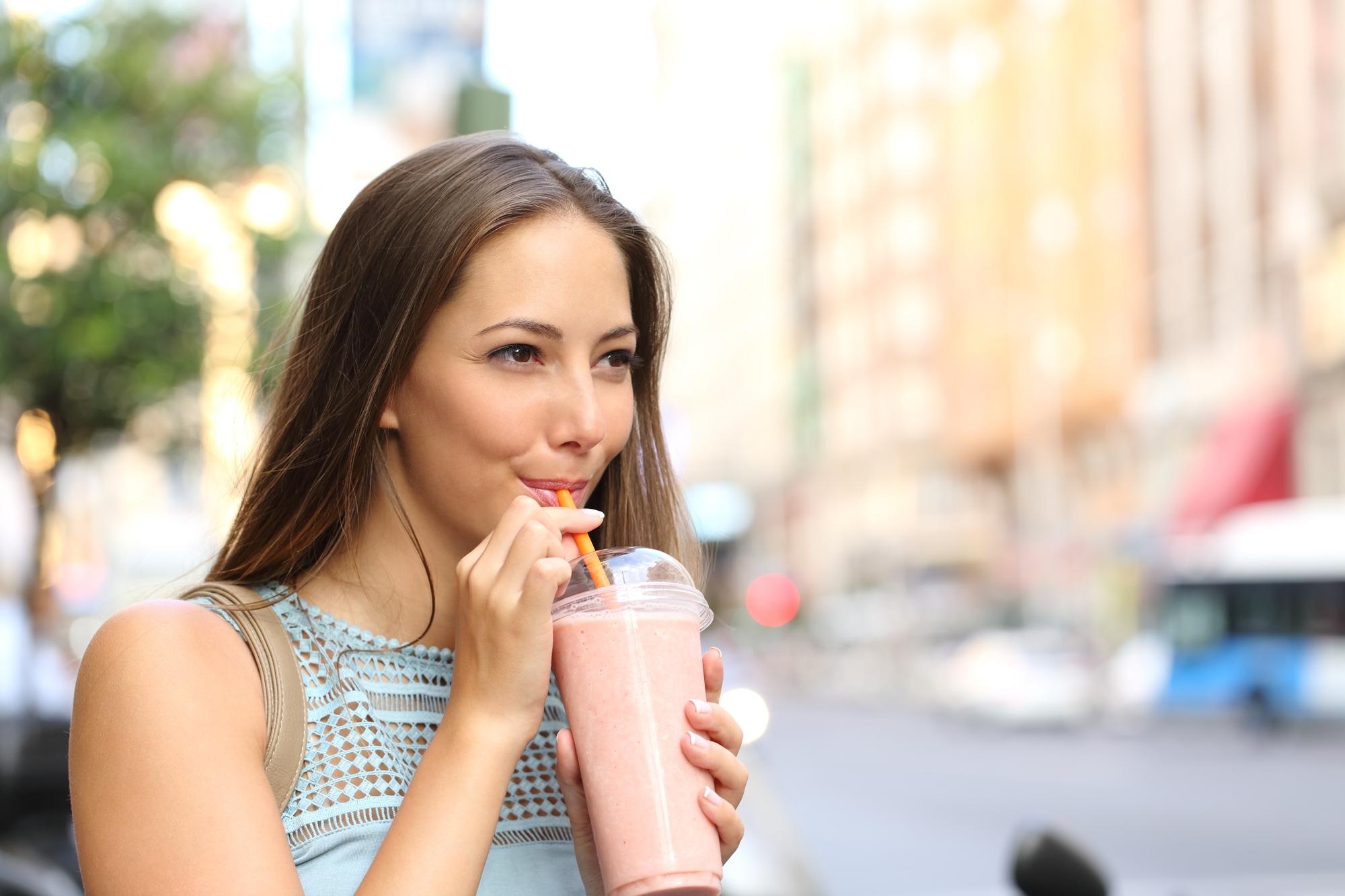 kobieta w mieście, latem, pijąca shake'a, nadwrażliwość zębów