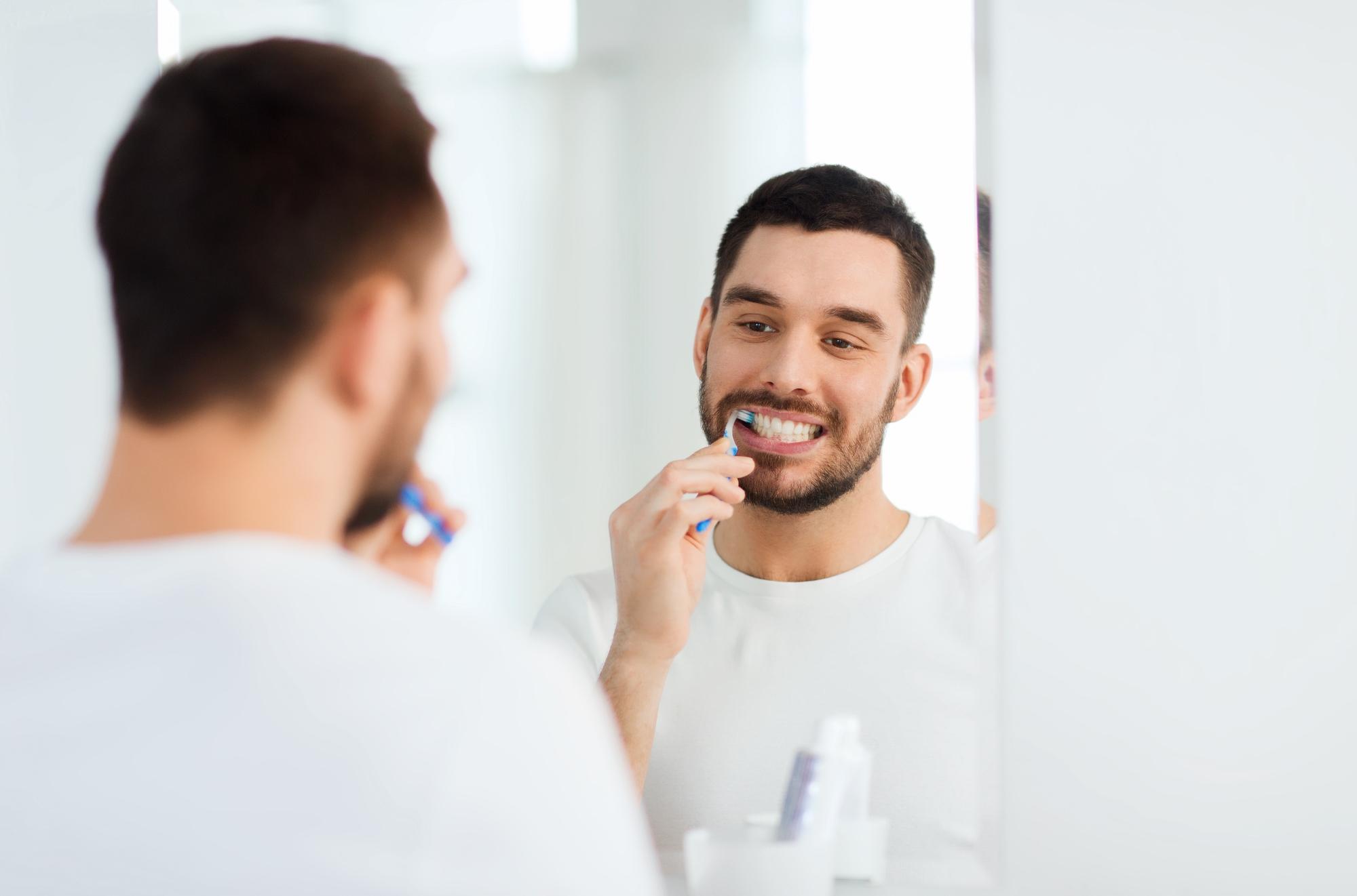 mężczyzna w łazience szczotujący zęby, nadwrażliwość zębów