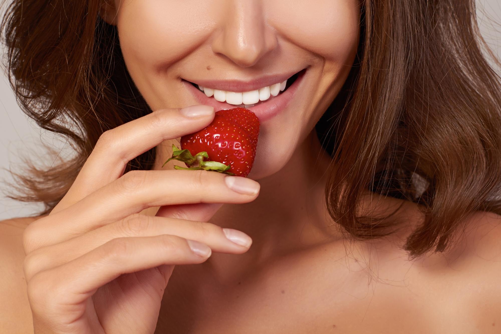 kobieta jedząca truskawkę